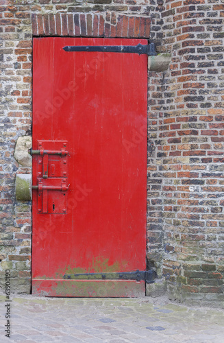 Red painted door with locks and brickwork wall