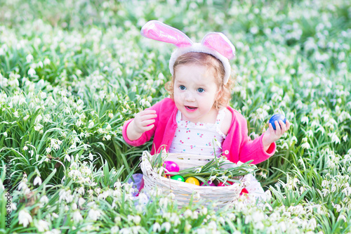 Adorable toddler girl wearing bunny ears playing with Easter egg
