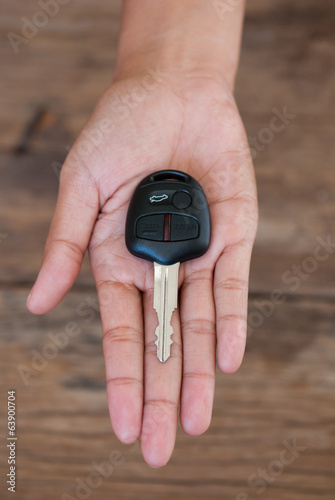 Hand with a car key on wood background
