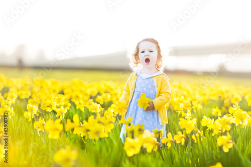Pretty toddler girl in a blue dress singing in field of flowers
