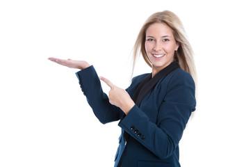 Lachende junge Frau präsentiert etwas mit der Hand