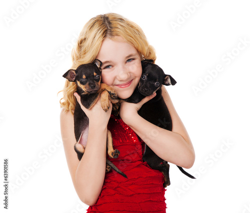 blonde smiling little girl holding two puppies
