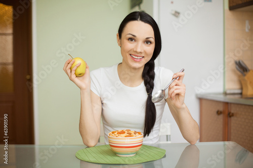 smiling girl having breakfast with muesli and apple