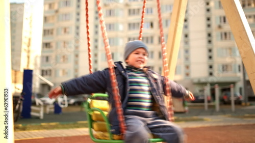 Happy boy swinging on a swing