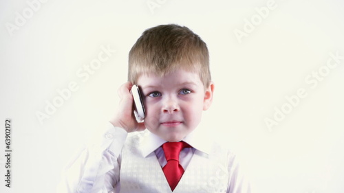 Boy six years in business suit talking on the phone