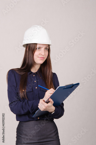 Girl a helmet writes in pencil folder