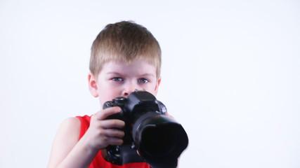 Мальчик шести лет с фотокамерой снимает