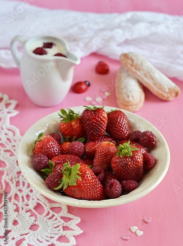 Strawberries and raspberries in a plate on pink background