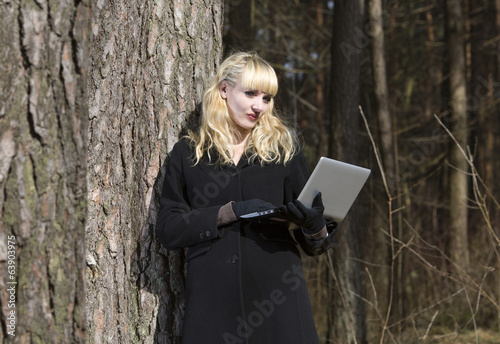 Portrait of the woman from laptops at a tree in the wood