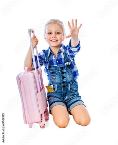 portrait of a little girl collects suitcase vacation rental