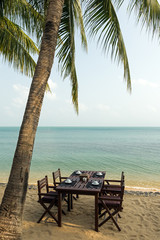 Table and chairs under a palm tree at a beach