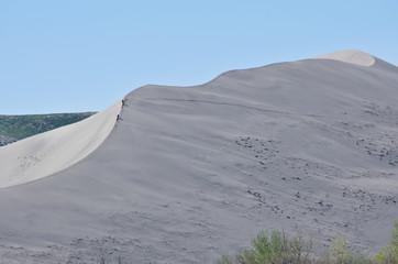 Explorers Hiking Across Sand Dune