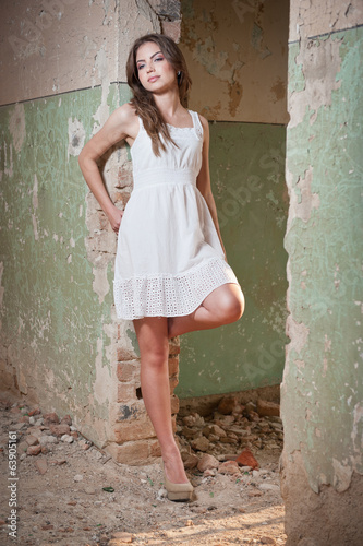 Beautiful girl posing fashion near an old wall