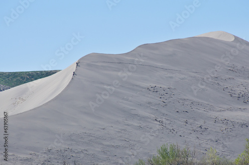 Explorers Hiking Across Sand Dune