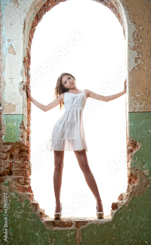 Beautiful girl posing fashion in a window frame