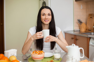 brunette girl drinking tea in the moring in the kitchen