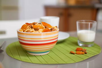 bowl with muesli and a glass of milk on the table