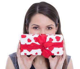 Junge Frau hält sich ein Geschenk mit roten Herzen vor Augen