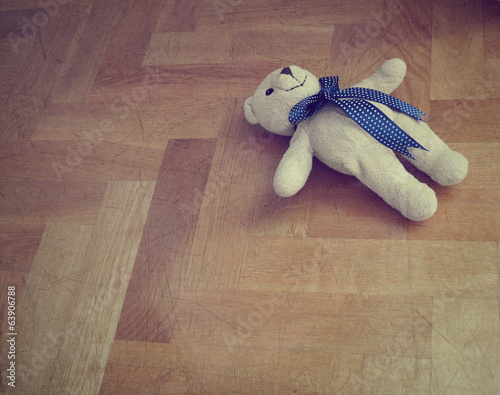 Lonely teddy bear on the floor - retro styled
