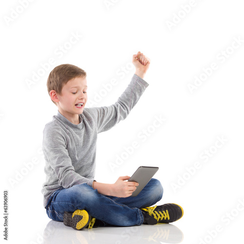 Happy boy using a tablet.