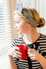 Pretty conceived woman enjoying cup of coffee