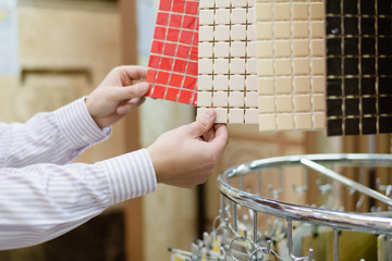 employee presenting colorful tiles in a supermarket