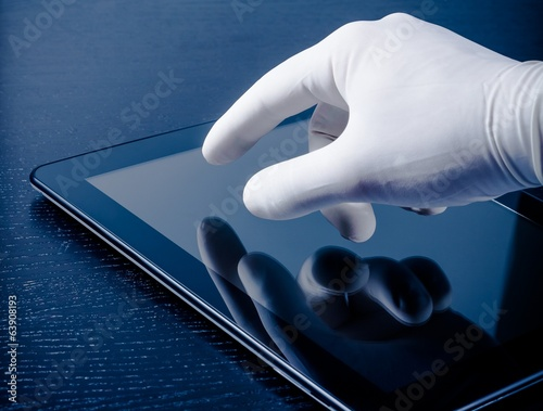 hand in medical glove touching modern digital tablet pc