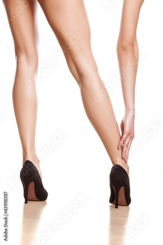 sexy woman touching her ankle on white background