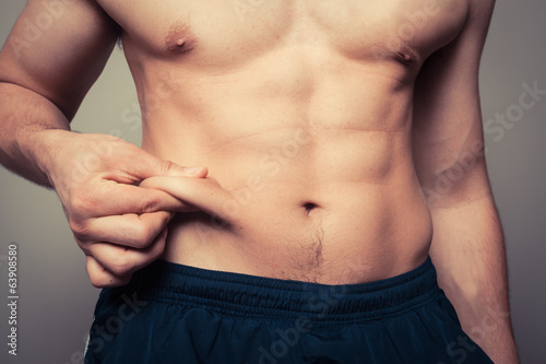 Valokuva Fit young man pinching his stomach