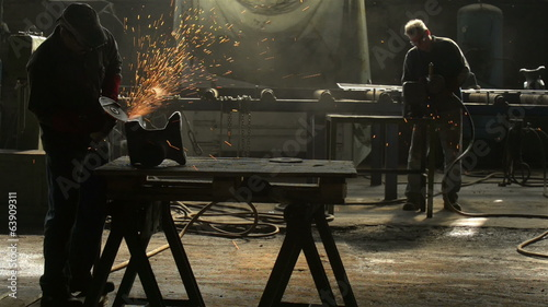 Worker cutting metal in the factory