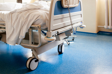 Empty hospital bed on hospital ward in a clean room