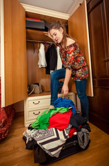 brunette woman packing clothes in big suitcase