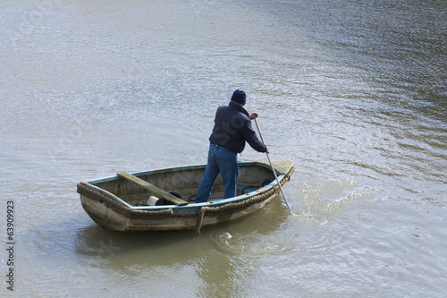 Single fishing man in small rowing boat