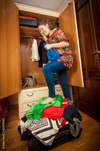 woman packing suitcase on holiday at wardrobe