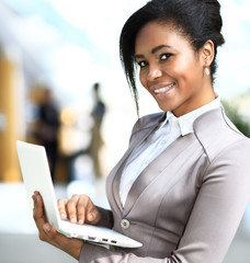 Business woman standing in foreground with laptop in her hands