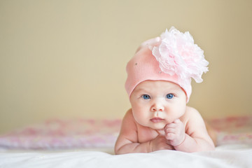 Serious cute baby in hat with flower