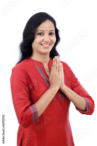 "Smiling young woman greeting ""Namasthe"""