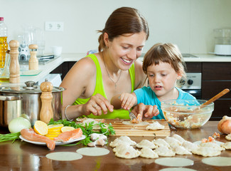 woman with a happy child makes Fish dumplings with salmon on the