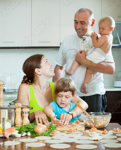 family of four together in the kitchen prepares food
