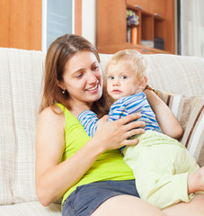 smiling  woman with toddler on sofa