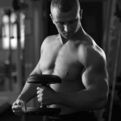 Muscular man working out with dumbbells looking to his biceps