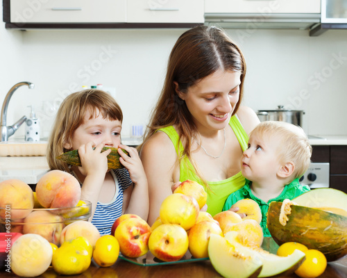 woman with  daughters eating melon and peaches
