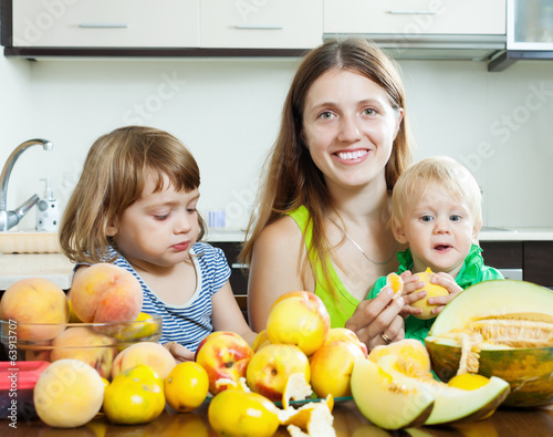 mother with children eating melon and other fruits