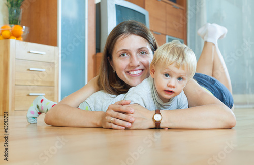 smiling woman with toddler on  floor