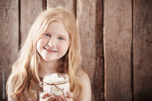 canvas print picture Girl with  marshmallows on wooden background