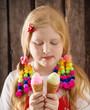 girl eating tasty ice cream over wooden background