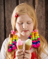 girl eating tasty ice cream over wooden background
