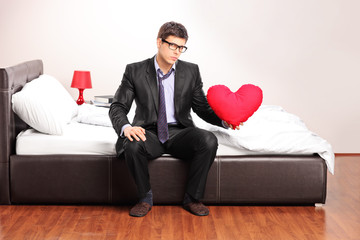 Formal man holding a red heart seated on bed