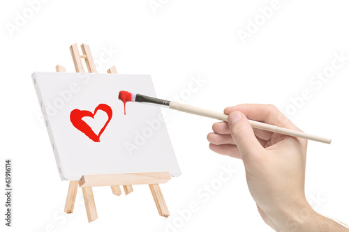 Hand with a paintbrush and a painting of a heart