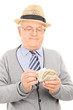 Male pensioner counting money